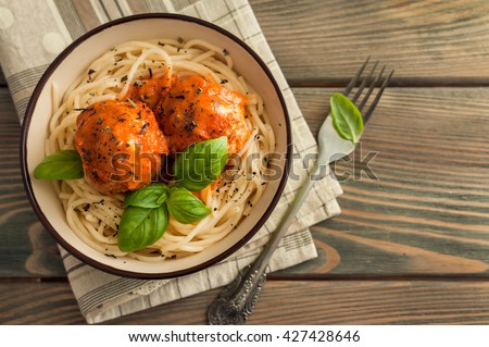 spaghetti and meatballs with tomato sauce on wooden background