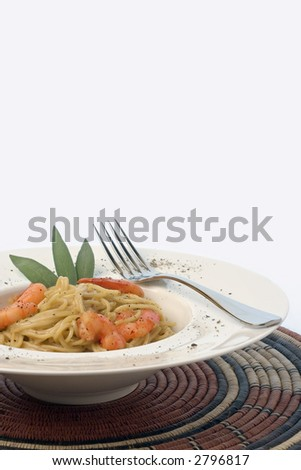 Spaghetti and prawns in a cream sauce, herb garnish. Served on a deep white, round bowl with wide rim sprinkled with ground pepper. Portrait view with layout space, isolate against white background. - stock photo
