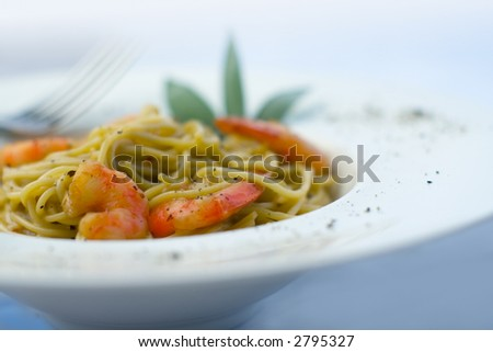 Spaghetti and prawns in cream sauce, herb garnish. On deep white, round bowl with wide rim sprinkled with ground pepper. Landscape with selective focus. Fade to white, bright background in blue light.