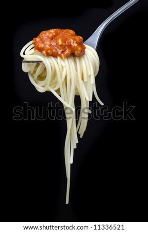 Spaghetti and sauce isolated over black background