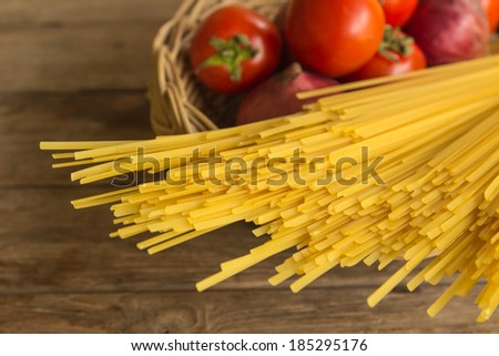 Spaghetti and tomato  in basket on wooden background - stock photo