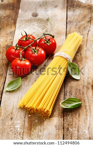Spaghetti and tomatoes with copyspace on a wood background - stock photo