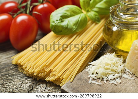 Spaghetti and tomatoes with parmesan cheese on a vintage wooden table close up - stock photo
