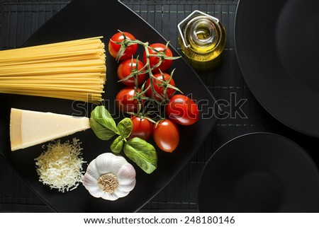 Spaghetti and tomatoes with parmesan cheese on black table - stock photo