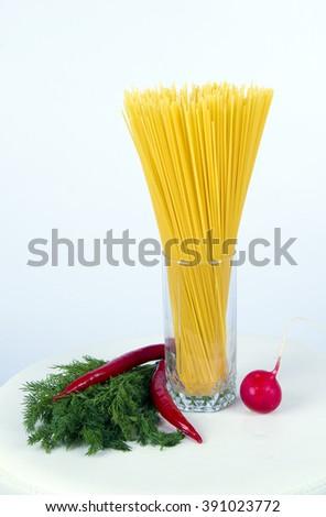 Spaghetti and vegetables ,dill and spaghetti ,spaghetti in glass ,yellow spaghetti ,green leaves dill ,radish,fresh vegetables, red vegetables ,green vegetables ,tasty vegetables,spring vegetables - stock photo