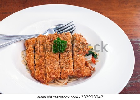 Spaghetti basil sauce with fried pork in white plate on wooden table