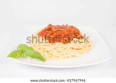 Spaghetti bolognese decorated with basil on a white background - stock photo