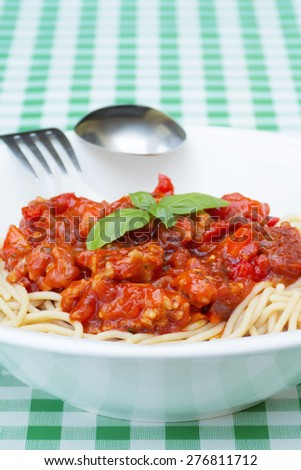 Spaghetti bolognese dish in white plate with fork and spoon on green checkered table - stock photo