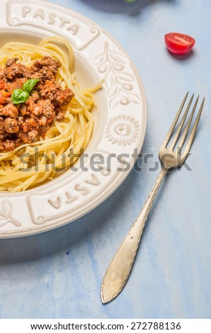 spaghetti bolognese in plate with the inscription : pasta and fork on blue wooden background, close up - stock photo