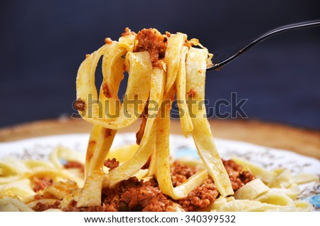 Spaghetti Bolognese on a fork, wooden table - stock photo