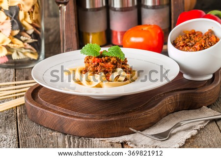 Spaghetti Bolognese on white plate, wooden background - stock photo