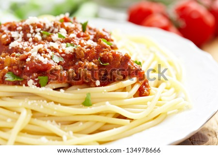 Spaghetti Bolognese on white plate, wooden table - stock photo