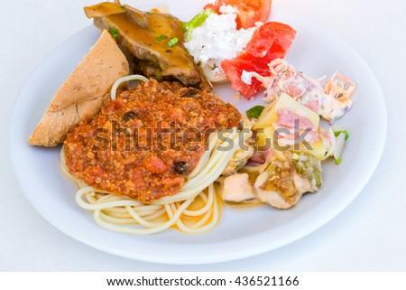 Spaghetti Bolognese with a Greek salad on a white plate. Bali, Rethymno, Crete, Greece - stock photo