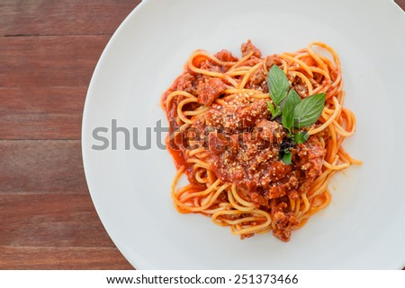 spaghetti bolognese with basil garnish - stock photo