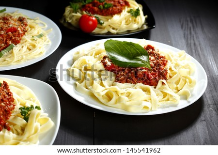 Spaghetti bolognese with basil in white plates on black table - stock photo