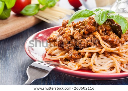 Spaghetti bolognese with cheese and basil on a plate - stock photo