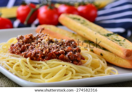 Spaghetti bolognese with garlic bread baguettes. - stock photo