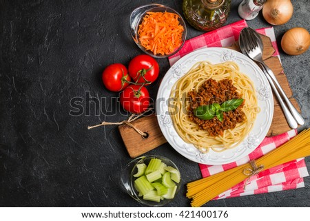 Spaghetti bolognese with ingredients on black background. Top view with copy space. - stock photo
