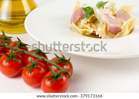 Spaghetti carbonara on a white dish with basil leaves, eggs yolk, cherry tomato, grated parmesan cheese and bacon traditional Italian recipe isolated white - stock photo