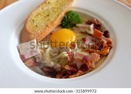 Spaghetti Carbonara topped with egg york and served with bread
