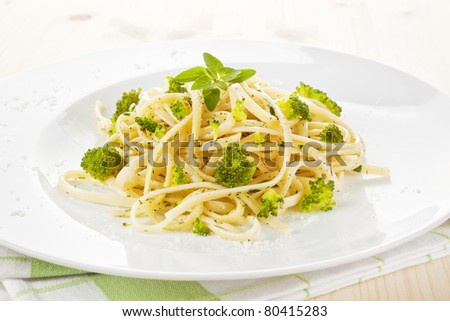 Spaghetti carborana with broccoli and fresh herbs on white plate. Traditional italian cuisine.