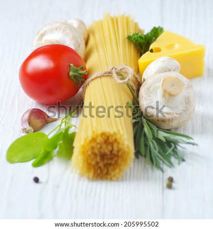Spaghetti, cheese, vegetables and herbs on a white wooden table. Ingredients Italian cuisine.