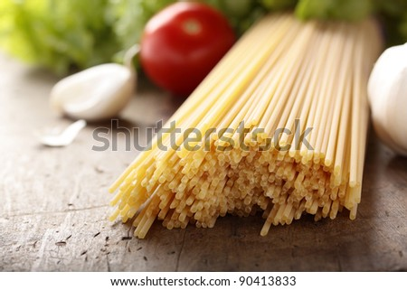 Spaghetti, garlic, cherry tomatoes & lettuce on a wooden chopping board. - stock photo