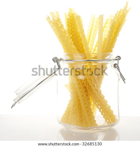 Spaghetti in glass jar on white background.