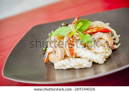 Spaghetti Mixed Seafood in the brown plate on red table - stock photo