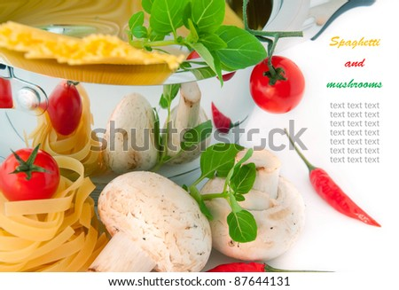 Spaghetti, mushrooms and tomatoes in a pan, a basil branch