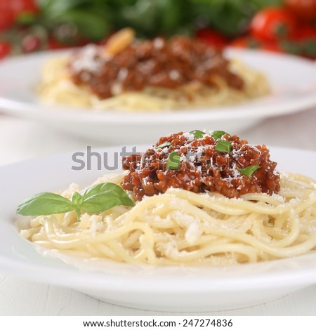 Spaghetti noodles pasta with Bolognese sauce meal with tomatoes on a plate - stock photo