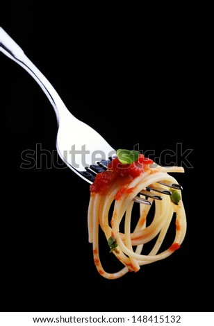 Spaghetti on a fork with tomato sauce and thyme - stock photo