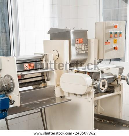 Spaghetti pasta machine in commercial kitchen - stock photo