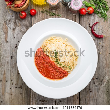 Spaghetti pasta with meatballs, tomato sauce, grated parmesan cheese and fresh basil - healthy homemade italian pasta on rustic wooden background with copy space, on a wooden table