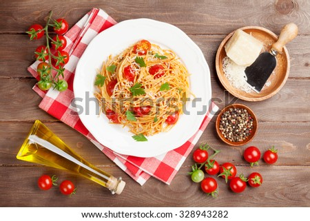 Spaghetti pasta with tomatoes and parsley on wooden table. Top view - stock photo