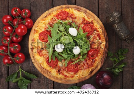 Spaghetti pizza margherita topped with fresh mozzarella cheese and rocket salad