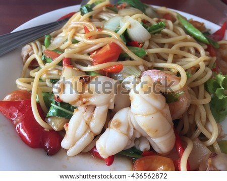 spaghetti seafood with spices, herbs of Thailand delicious food hot and spicy Thai as Italian mix style. stir-fried spicy spaghetti with seafood. thai style stir-fried spicy seafood pasta. close up  - stock photo