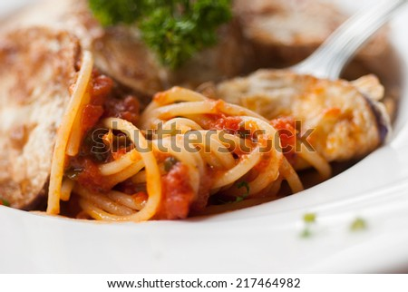 Spaghetti with a slice of grilled eggplant served on a white plate