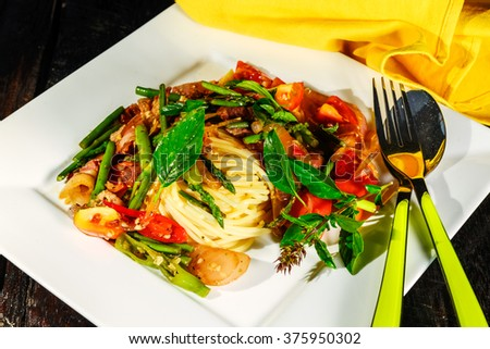 spaghetti with asparagus tomatoes bacon and herbs on wood table and white plate