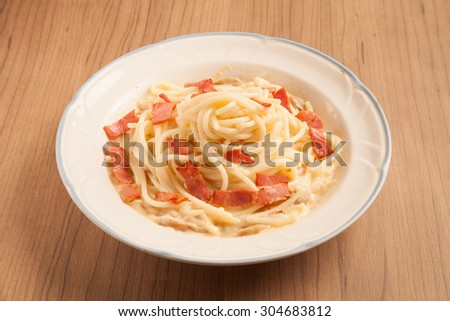 Spaghetti with bacon and cream sauce on plate. - stock photo