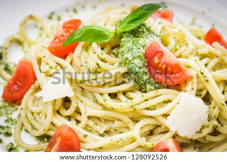 Spaghetti with green pesto, parmesan and cherry tomatoes - stock photo