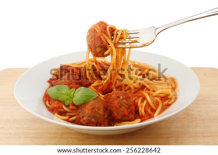 Spaghetti with meat balls in a bowl with a fork on a wooden board - stock photo