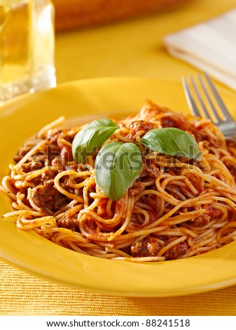 spaghetti with meaty sauce with basil garnish on a yellow plate.. shot with selective focus