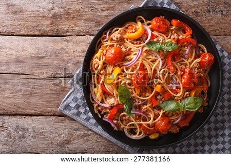 Spaghetti with minced meat and vegetables. horizontal top view, rustic style  - stock photo