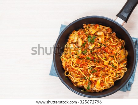 spaghetti with mushroom and minced meat in a frying pan
