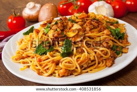 spaghetti with mushroom, vegetables and minced meat in a plate on wooden table - stock photo