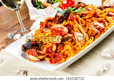 Spaghetti with mussels and tomato sauce on wooden table on evening light