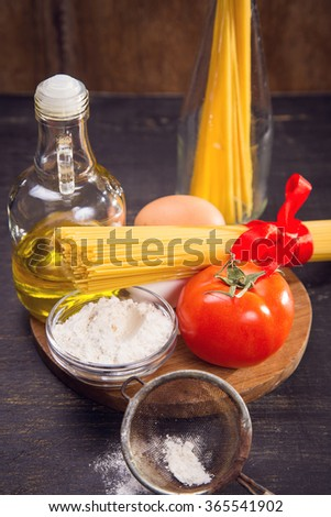 spaghetti  with oil,flour,eggs and tomatoes in studio