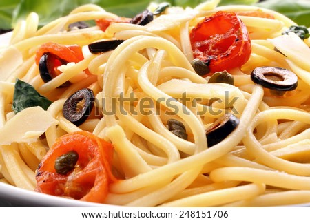 Spaghetti with olive sauce and tomatoes - stock photo