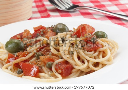 Spaghetti with olives and tomato - stock photo